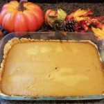 Pumpkin Pie Bar in a Pyrex Rectangular Baking Dish adorned with pumpkin decor and vibrant fall leaves
